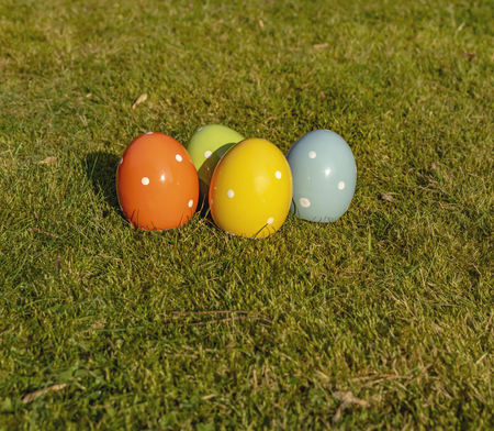 Colorful ceramic easter eggs lying on a meadow.