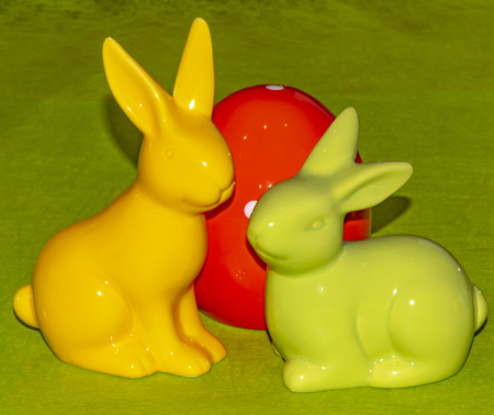 Colorful ceramic easter egg and two Easter bunnies in front of a green background