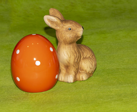 Colorful ceramic easter eggs and an Easter bunny in front of a green background Stock Photo