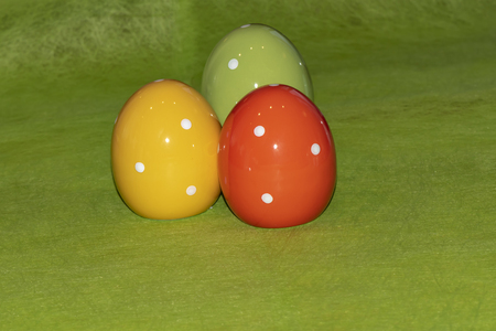 Colorful ceramic easter eggs in front of a green background Stock Photo