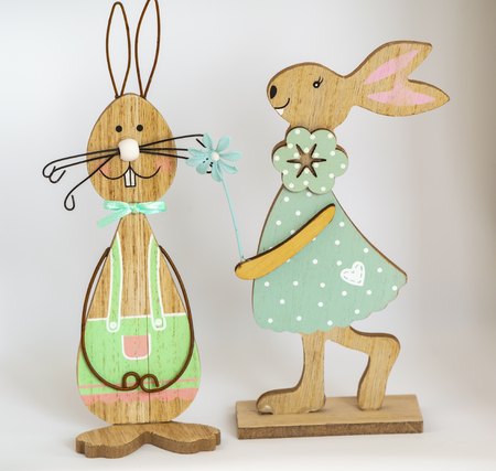 Two colorful wooden easter bunnies in front of a light background. Stock Photo