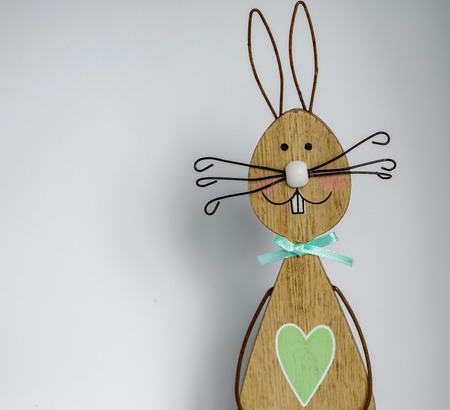 Wooden easter bunny in front of a light background as a basis for an Easter card.