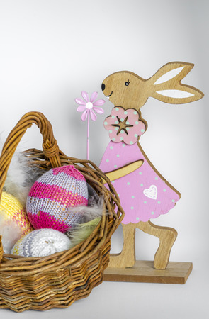 Colorful wooden easter bunny with a wicker basket filled with knitted easter eggs.