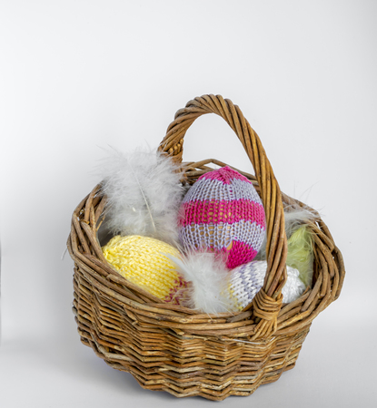 A wicker basket filled with knitted easter eggs in front of a light background as a basis for an Easter card.