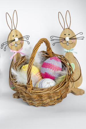 Two colorful wooden easter bunnies with a wicker basket filled with knitted easter eggs.