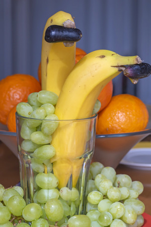 Fun food as a healthy snack with fruits: bananas as dolphins with a dark grape in the mouth and green grapes and tangerines as a decoration.