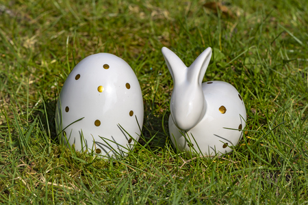 Easter bunny and Easter egg made of white pottery with golden polka dots on a meadow. Stock Photo