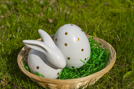 An Easter bunny and an Easter egg made of white pottery with golden polka dots in a basket on a meadow.