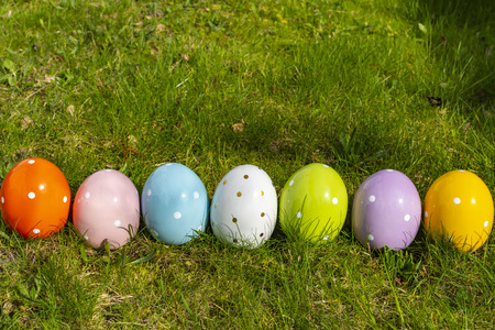 Colorful ceramic easter eggs in a line on a meadow.
