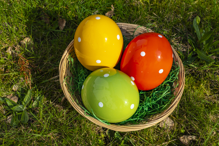 Colorful ceramic easter eggs in a basket on a meadow. Stock Photo