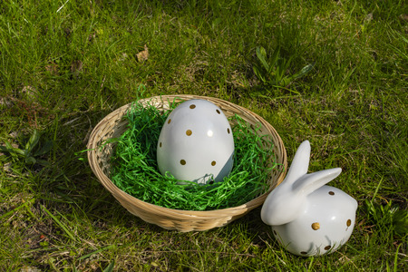 An Easter bunny and an Easter egg made of white pottery with golden polka dots with a basket on a meadow. Stock Photo