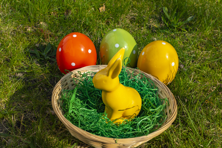 A yellow Easter bunny and colorful Easter eggs made of pottery with a basket on a meadow. Stock Photo