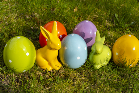 Colorful ceramic easter eggs and Easter bunnies on a meadow. Stock Photo