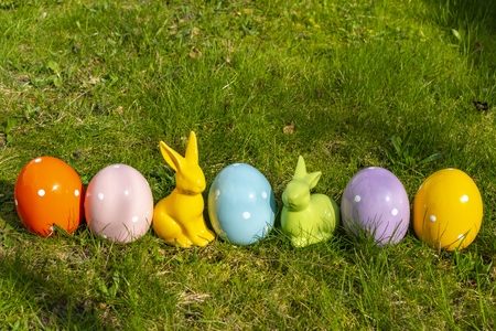 Colorful ceramic easter eggs and Easter bunnies in a line on a meadow. Stock Photo