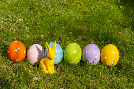 Colorful ceramic easter eggs and an Easter bunny in a line on a meadow.