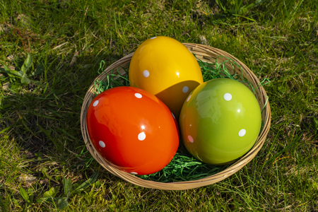 Colorful ceramic easter eggs in a basket on a meadow.