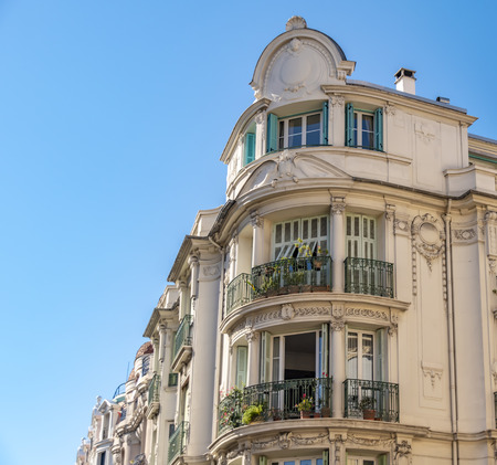 View to the decorated facade of a historic house in Nice, France. You can see the typical windows, balconies and shutters of a Mediterranean cityscape.