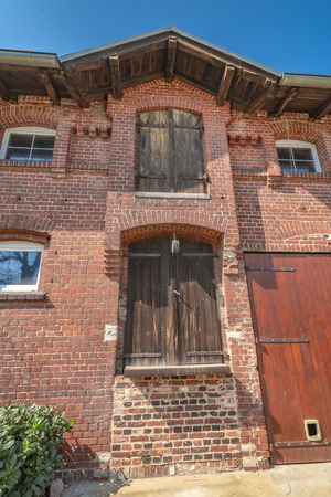 Detail view of an old farm. The facade is made of brick. In it are old wooden gates, which were used for loading and unloading of barn and storage. Editorial