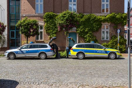 Dannenberg, Germany - May 23, 2019: Two German police cars parked on the roadside of a medieval city with the tailgates open, while two policemen reload material. Redactioneel