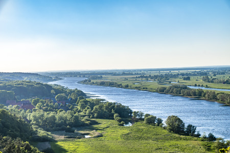 View over the Elbauen in Lower Saxony, Germany. You see a landscape with fields, meadows and the river Elbe under a blue sky.