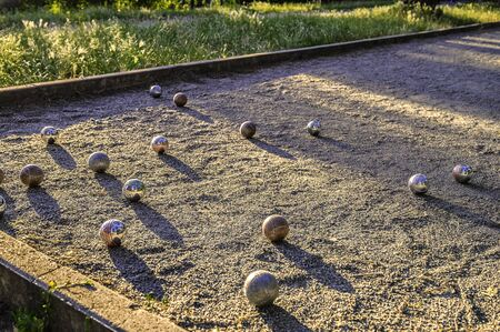 Photo of a playing field for boules in a public park in the middle of Berlin at dusk.