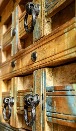 Details of a wooden chest made of recycled old ship planks with rivets and metal rings.