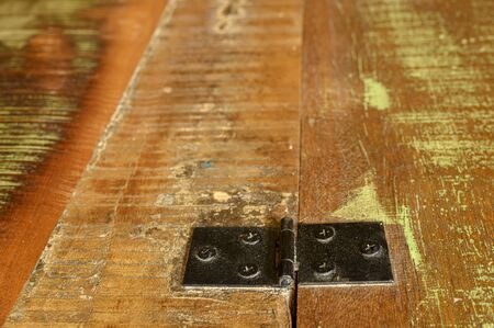 Hinge on the surface of a wooden chest of recycled old ship planks. Фото со стока