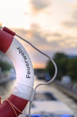 Part of a lifebuoy with rope. In the blurry background you can see a river on which a boat is driving, and the sky lit by the evening sun. The text on the ring is German for fire department. Stock fotó