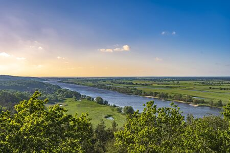 View over the Elbauen in Lower Saxony, Germany. You see a landscape with fields, meadows and the river Elbe under a blue sky with clouds, which are illuminated by the sun.
