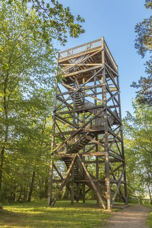 View to a wooden observation tower between trees on a sunny day.