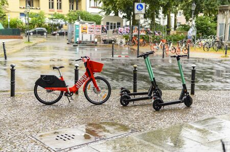 Berlin, Germany - July 13, 2019: Parked rental bicycles and rental scooters on a square in downtown Berlin on a rainy day. Editorial