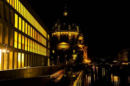 Night shot of downtown Berlin near the river Spree with cathedral and Humboldt Forum. The lights of the buildings are reflected in the river.