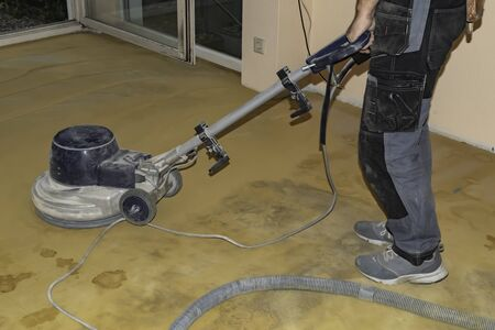 Worker using a grinder to prepare the floor for a new flooring.