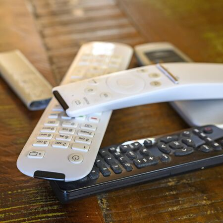 Various remote controls lying on a wooden table on top of each other.