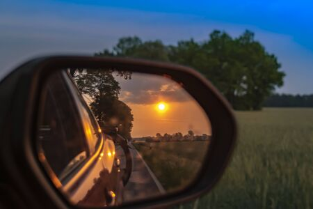 Look in the outside mirror of a moving car. In the mirror you can see the setting sun, parts of the vehicle and a bicycle at the rear.