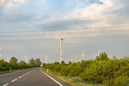 Wind farm with many wind turbines beside a country road in Lower Saxony, Germany. Stok Fotoğraf
