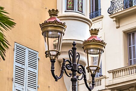 Historic two-armed street lamp in Nice, France, in front of a house facade with wooden shutters.
