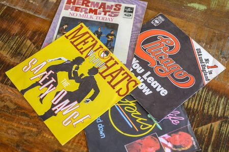 Berlin, Germany - August 25, 2019: Some record covers from the sixties to the eighties on a wooden table.