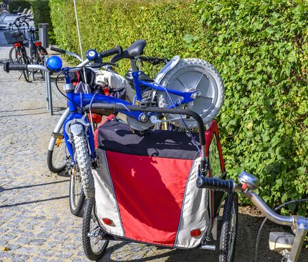 Bansin, Germany - September 13, 2019: Parked bicycles in the coastal town of Bansin on the island of Usedom, Germany. A childrens bicycle was piggybacked on the bike trailer.