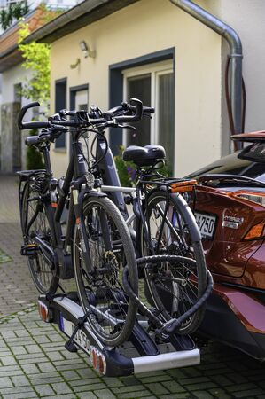 Bansin, Germany - September 14, 2019: Parked car with a bike carrier attached to the stern and two bicycles mounted on it.