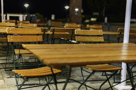 View to a group of wooden patio furniture on the terrace of a restaurant. Zdjęcie Seryjne