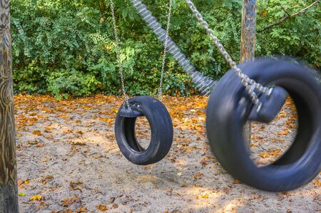 Childrens playground in Germany - view to two tire swings, of which the tire in the foreground rushes past blurred. Banco de Imagens