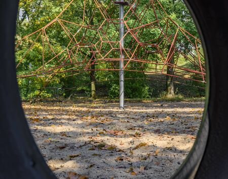 Childrens playground in Germany - view through a tire swing to a climbing frame in the background.