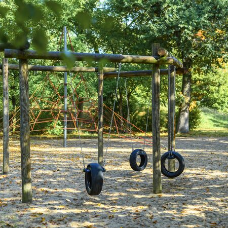 Childrens playground in Germany with a tire swing and a climbing frame in the background.