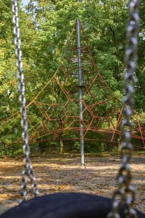 Childrens playground in Germany - view between the chains of a tire swing to a climbing frame in the background. Banco de Imagens