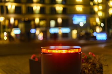 A retractable bollard with a red warning light as a barrier to a pedestrian area at night in Bansin, Germany. In the background you can see points of light from houses and shops.