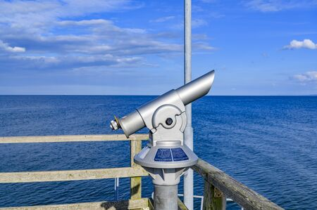 Telescope with coin slot on the pier in Bansin on the island of Usedom in Germany. Sea and sky are dark blue and radiate in the sunshine.