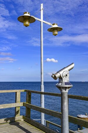 Telescope with coin slot and lantern on the pier in Bansin on the island of Usedom in Germany. Sea and sky are dark blue and radiate in the sunshine. Stok Fotoğraf
