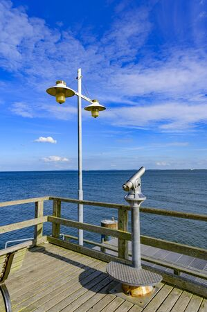 Telescope with coin slot and lantern on the pier in Bansin on the island of Usedom in Germany. Sea and sky are dark blue and radiate in the sunshine. Banque d'images