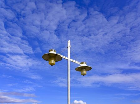 A two-armed lantern in front of a blue sky with clouds. Фото со стока